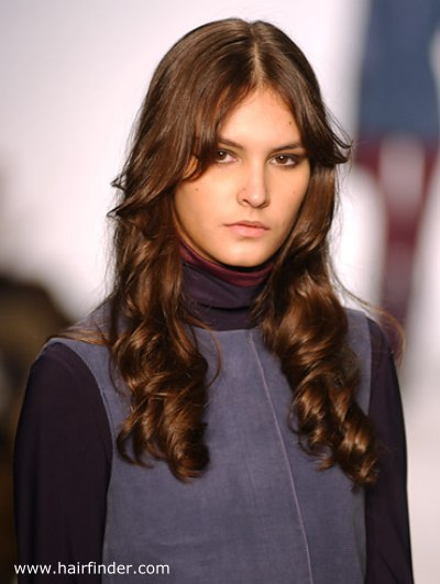 Long brunette hair with soft coils and side-swept bangs