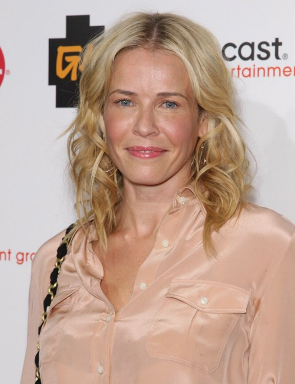Chelsea Handler With Her Hair In Curls And Wearing A Pink Silk Blouse Dress