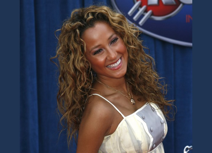 Adrienne Bailon with long hair styled into curls