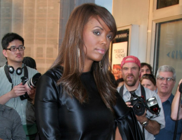 Aisha Tyler wearing a shiny black mini dress