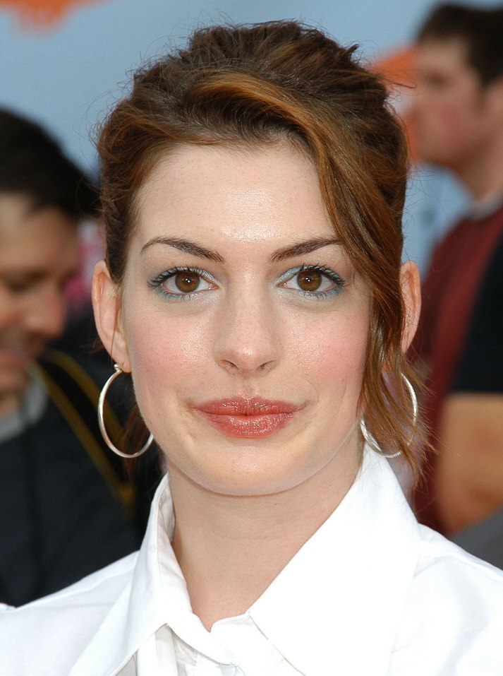 Anne Hathaway Wearing A Blouse With Loosely Bound Tie And A Youthful