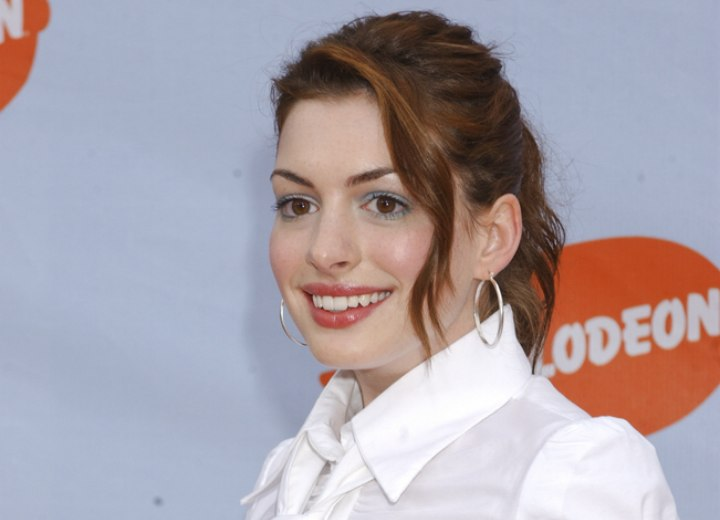 Anne Hathaway wearing a blouse and necktie