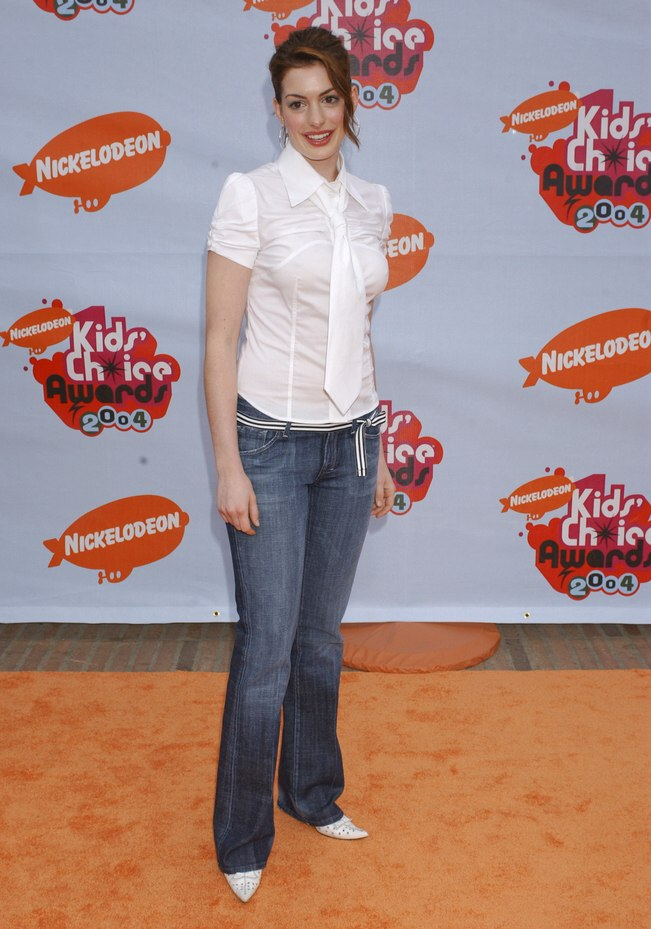 Anne Hathaway Wearing A Blouse With Loosely Bound Tie And A Youthful Ponytail