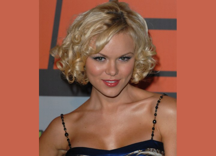 Anya Monzikova with short curly hair and wearing a spaghetti straps dress