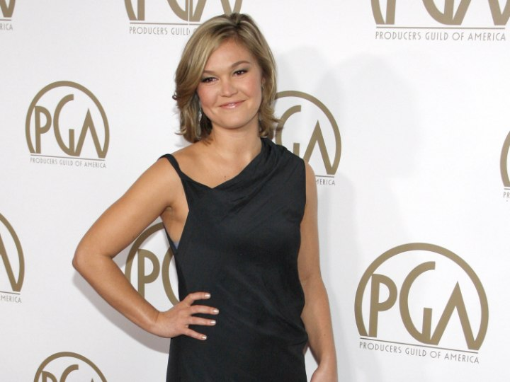 Julia Stiles wearing a black cocktail dress with an asymmetrical neckline
