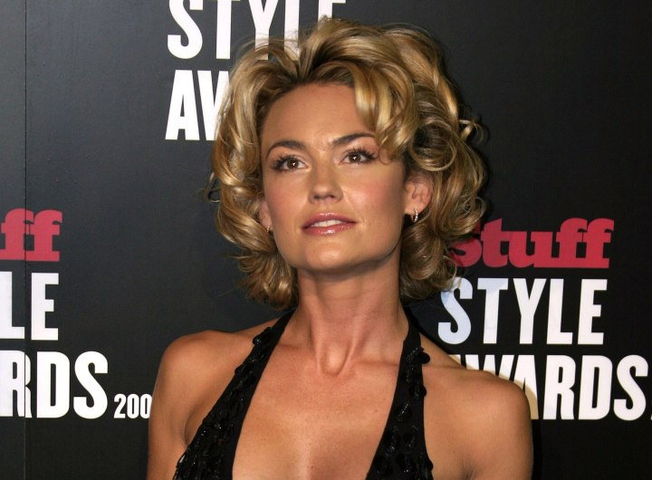 Kelly Carlson with a short curly hairdo
