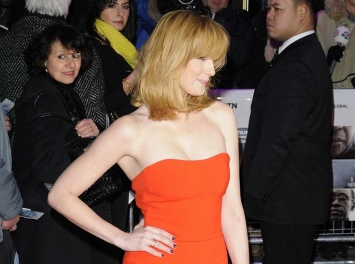 Kelly Reilly wearing an orange form-fitting gown