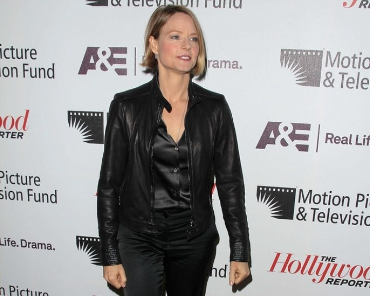 Jodie Foster wearing a satin blouse and leather jacket