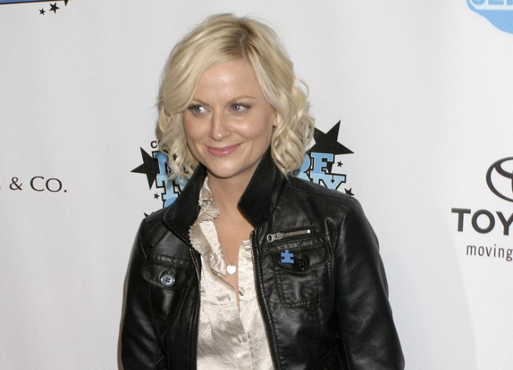 Amy Poehler wearing a shiny blouse and a leather jacket with stand up collar