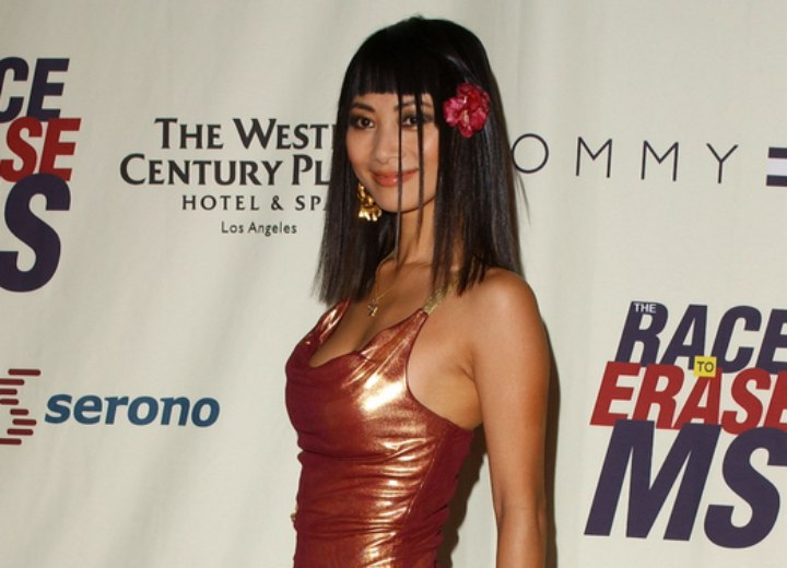 Bai Ling wearing a shimmery dress with angled skirt