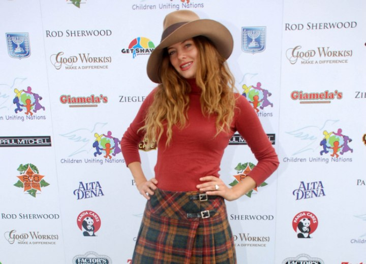 Bijou Phillips wearing a turtleneck, skirt and boots