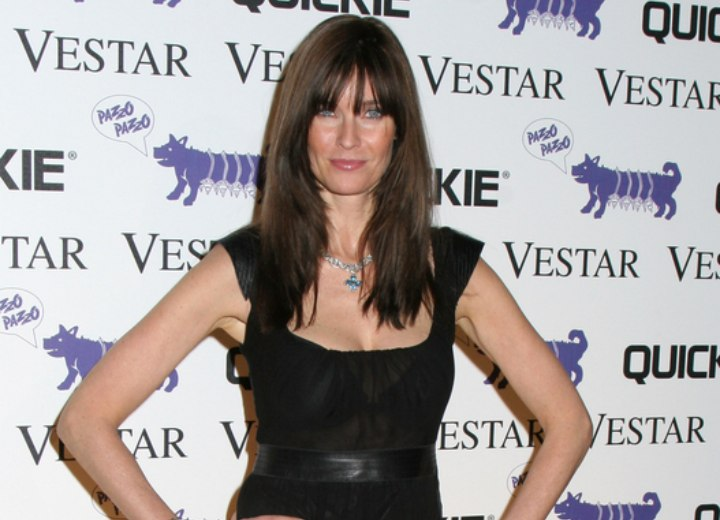 Carol Alt wearing a black dress and boots