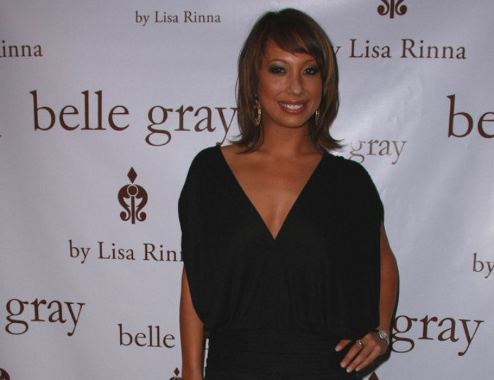 Cheryl Burke wearing high heel boots and a V-neck top