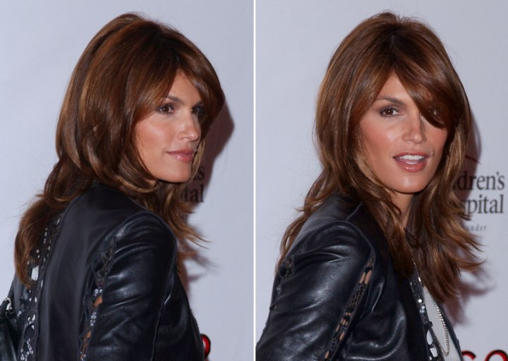 Back and side view of Cindy Crawford's long layered hairstyle