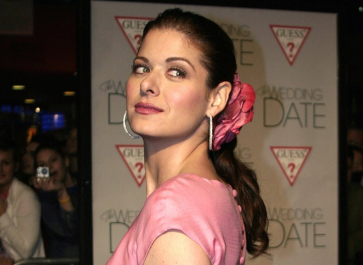 Debra Messing wearing a black and pink dress and a flower in her hair