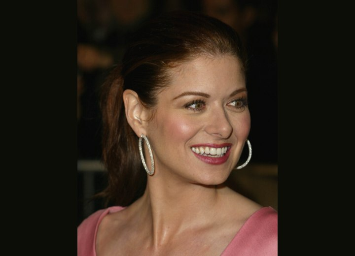 Debra Messing with her hair pulled into tight ponytail