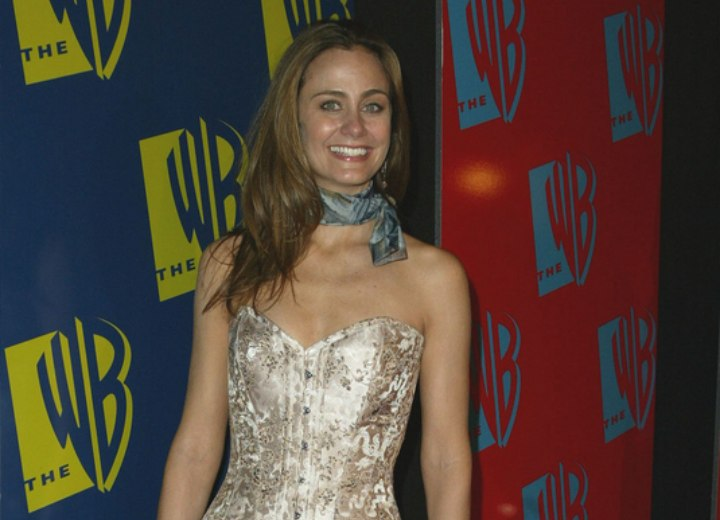 Diane Farr wearing a shiny brocade corset top with trousers and a scarf