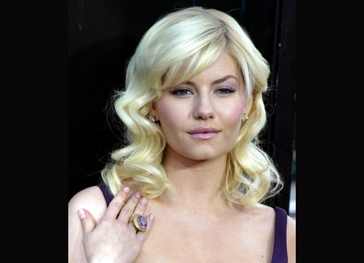 Elisha Cuthbert with curled blonde hair and bangs