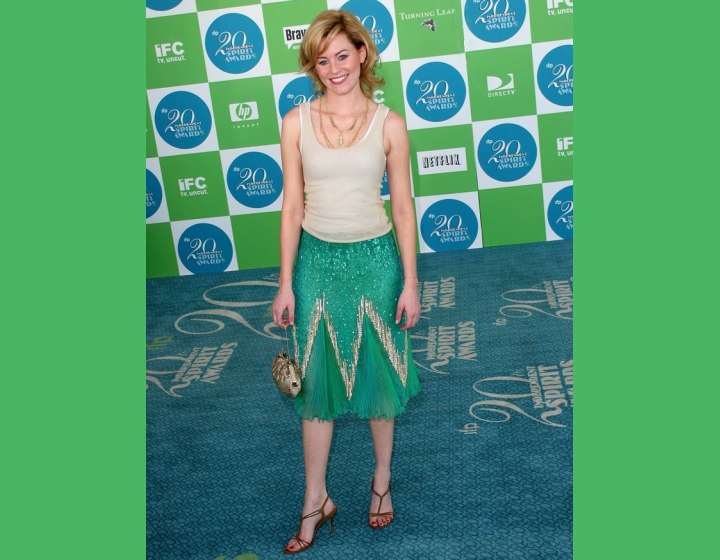 Elizabeth Banks wearing a green skirt and a tank top