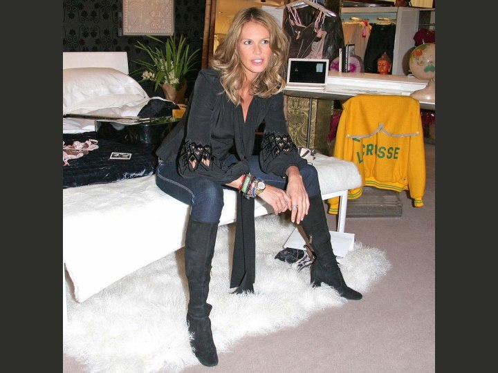 Elle MacPherson wearing a silk blouse, jeans and boots