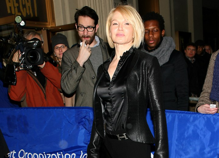 Ellen Barkin wearing a black silk blouse, jacket and trousers