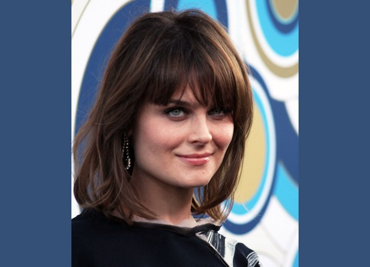 Hairstyle with long angled bangs ending upon the temple - Emily Deschanel