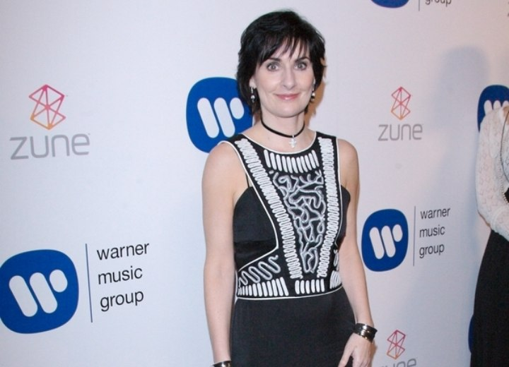 Enya wearing a black and white dress with long skirt