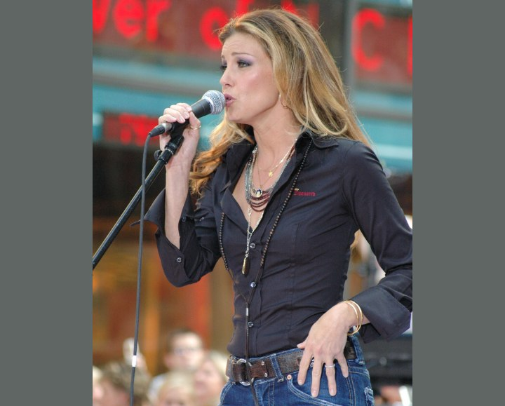 Faith Hill with very long hair and wearing a shirt, belt and jeans