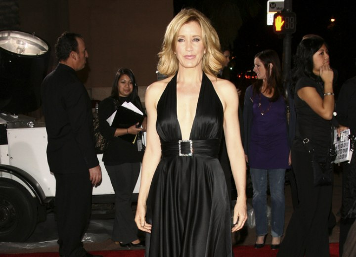 Felicity Huffman wearing a shiny black Marylin Monroe inspired dress