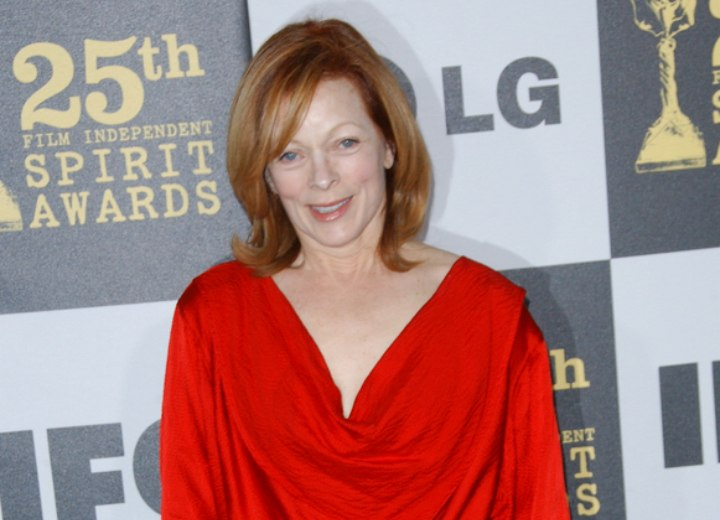 Frances Fisher wearing a silky red loose neck blouse
