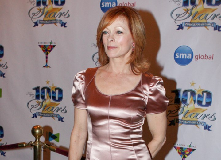 Frances Fisher with shoulder length hair and wearing a shiny dress