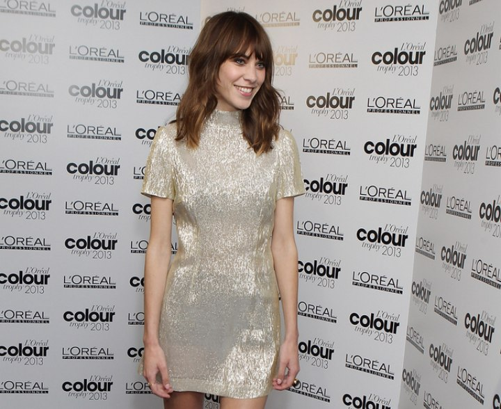 Alexa Chung wearing a gold mini dress with a high collar