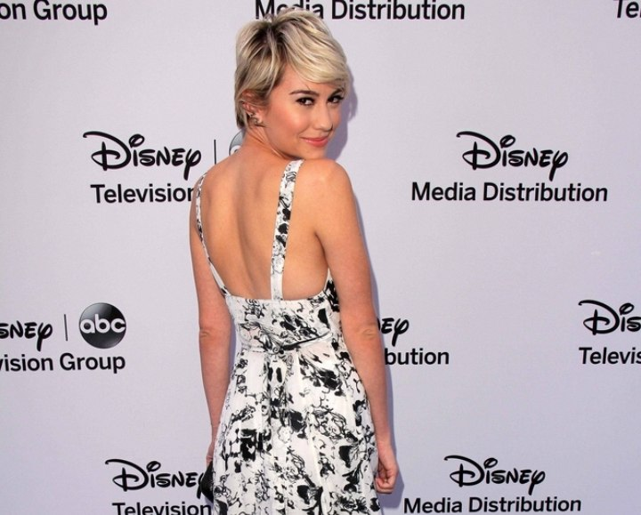Chelsea Kane with very short hair and wearing a long dress