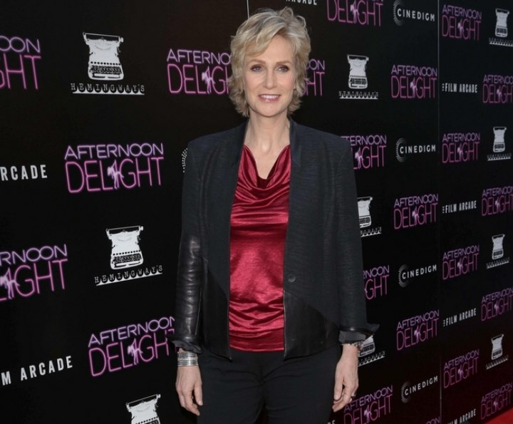 Jane Lynch wearing a shiny draped collar top