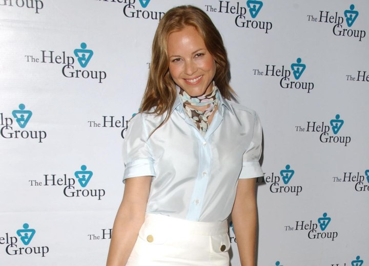 Maria Bello wearing a silk blouse, skirt and scarf