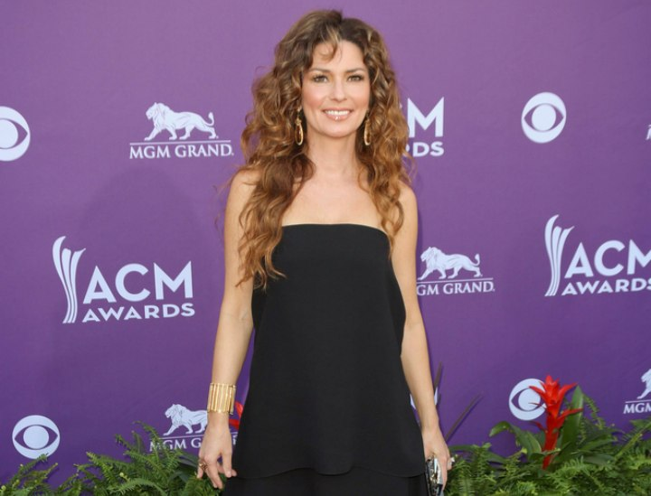Shania Twain waering high boots and a short black dress