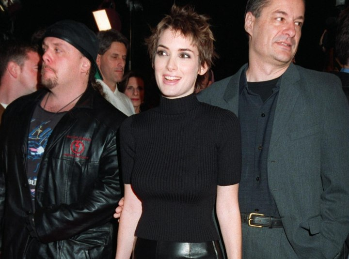Winona Ryder wearing a black turtleneck and leather skirt