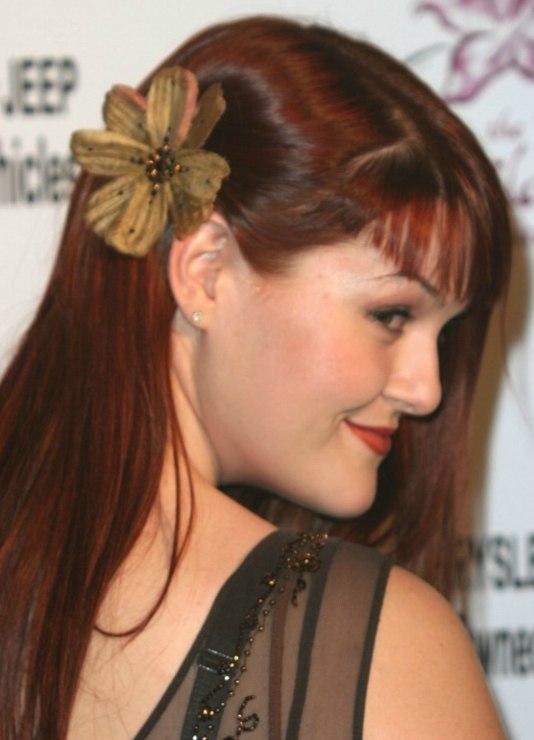 Sara Rues Long Sleek Hair With A Flower Behind Her Ear