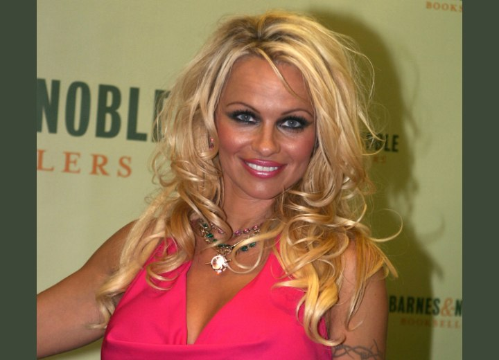 Pamela Anderson wearing a pink cowl neck top