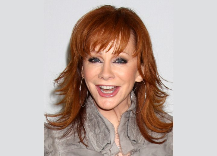 Reba McEntire wearing her red hair in a long chiseled style
