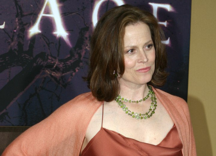 Sigourney Weaver wearing an orrange silk dress