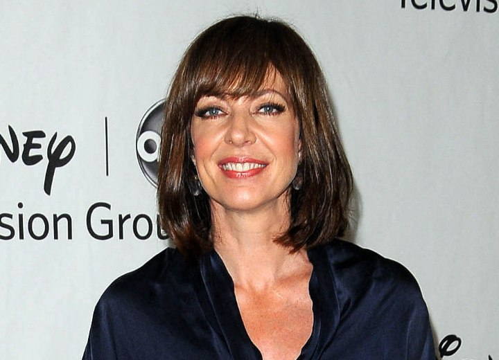Allison Janney wearing jeans and a navy silk blouse