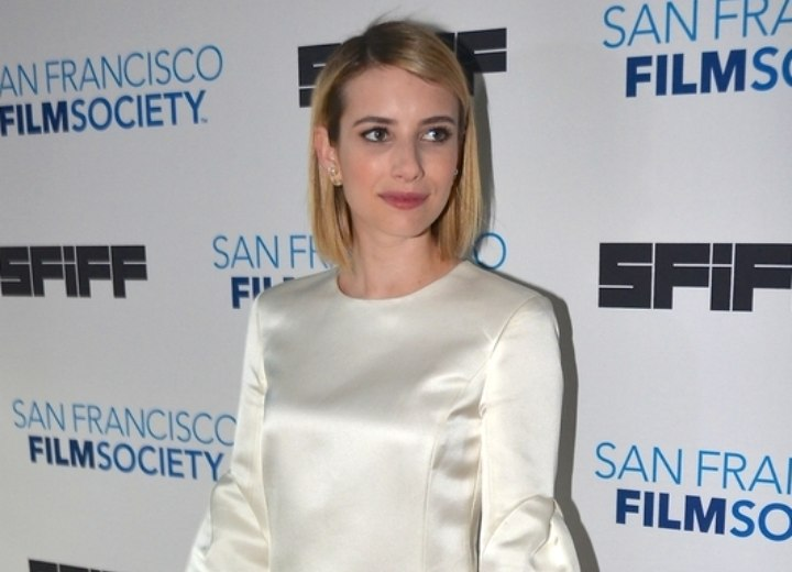 Emma Roberts wearing a white dress with a retro feel