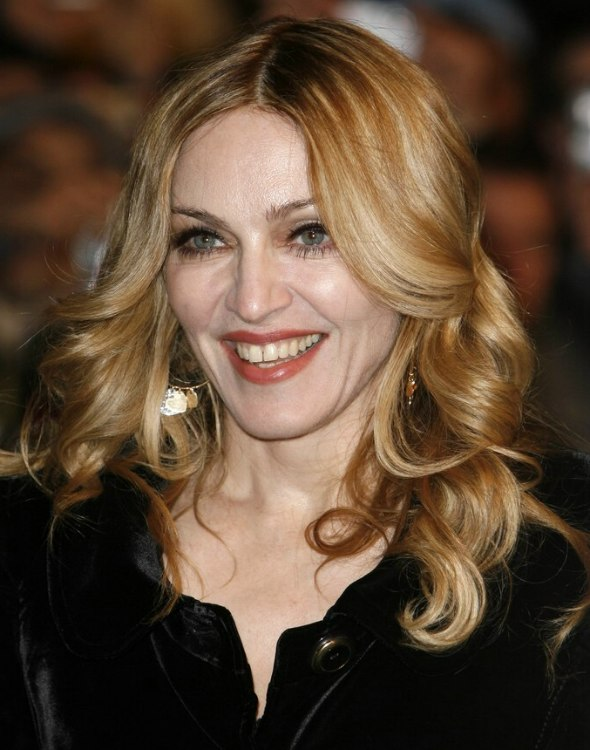 Madonna wearing her long blonde hair with foiled colors and curls