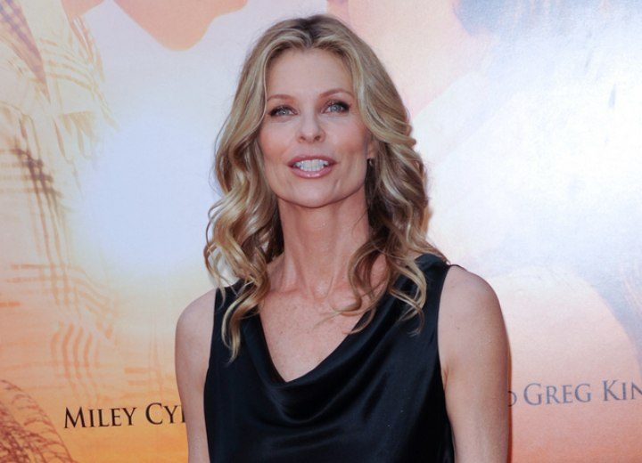 Kate Vernon wearing a silky black drape neck dress