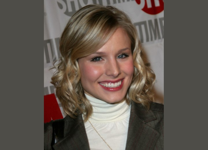 Kristen Bell wearing a white turtleneck and a pinstripe blazer