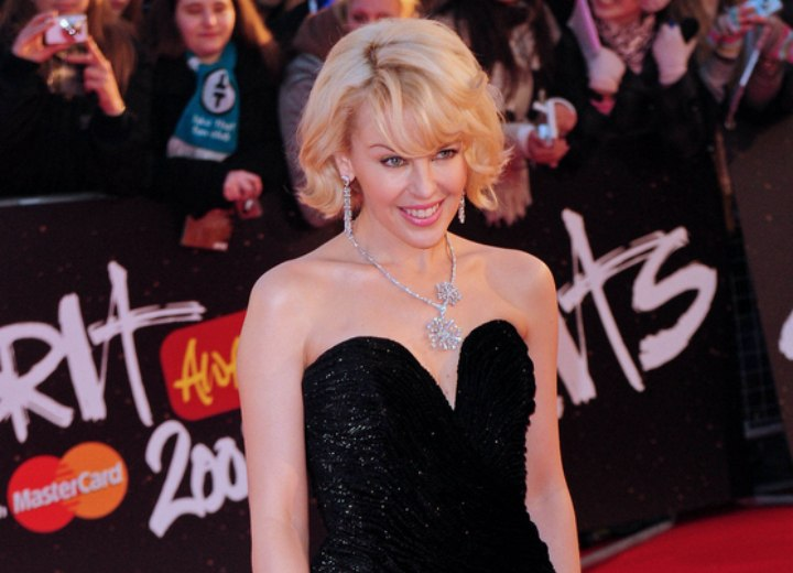 Kylie Minogue wearing a strapless black dress