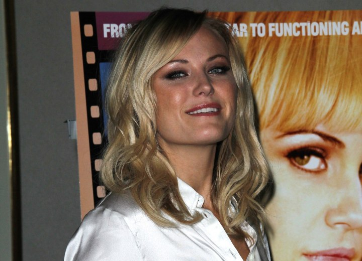 Malin Akerman's business look with long wavy hair and a silk blouse