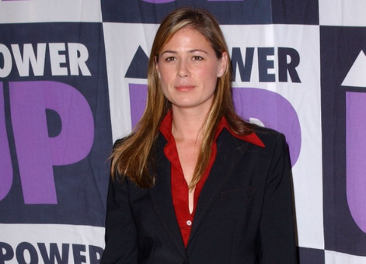 Maura Tierney wearing a red silk blouse and suit