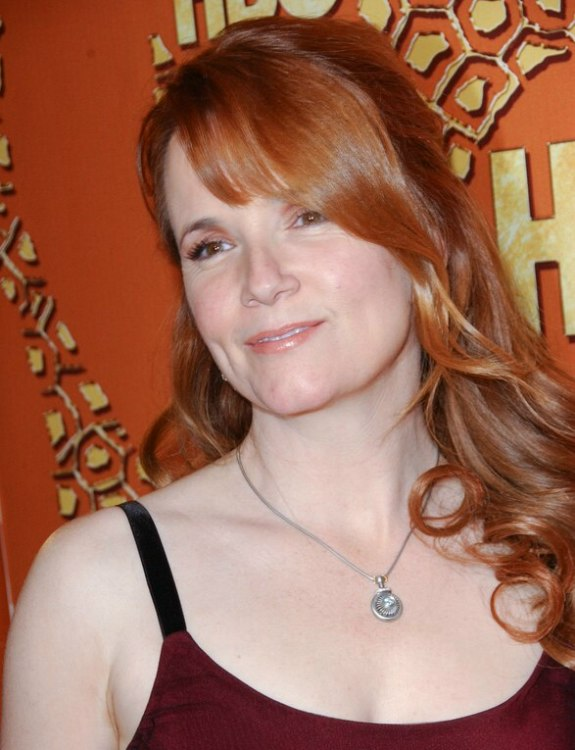 Lea Thompson with her long red hair worn over to one side and with ...